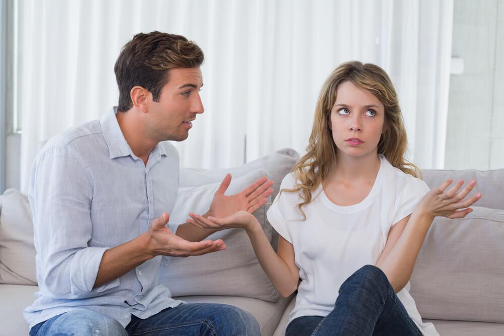 ソファに座り口論する夫婦