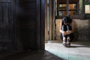 実習先から逃げ出したものの、途方に暮れて膝を抱えてなくアジア人女性