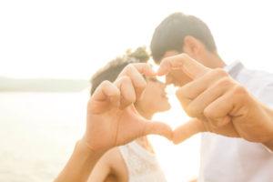キスをしながらお互いの手でハートを作る新郎新婦
