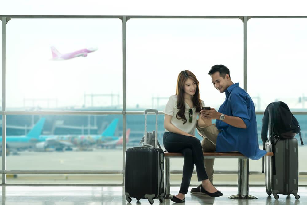 空港で座りながら談笑するアジア人カップル