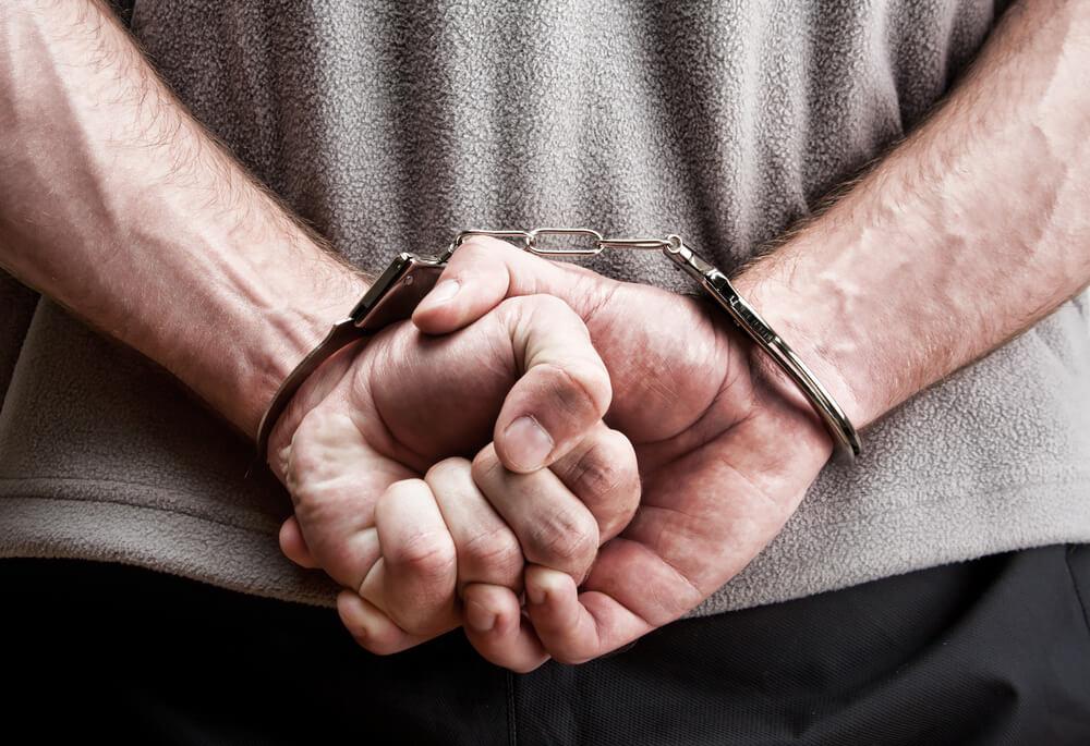 手錠で両手を背中で縛られている男性