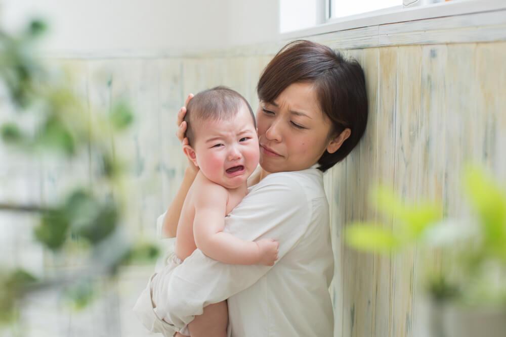 日本人のお母さんが、泣いている赤ちゃんを抱きかかえて困っている