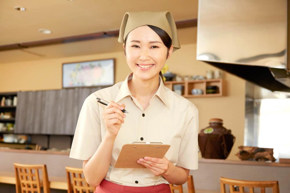 日本の居酒屋でアルバイトをする外国人留学生の女性