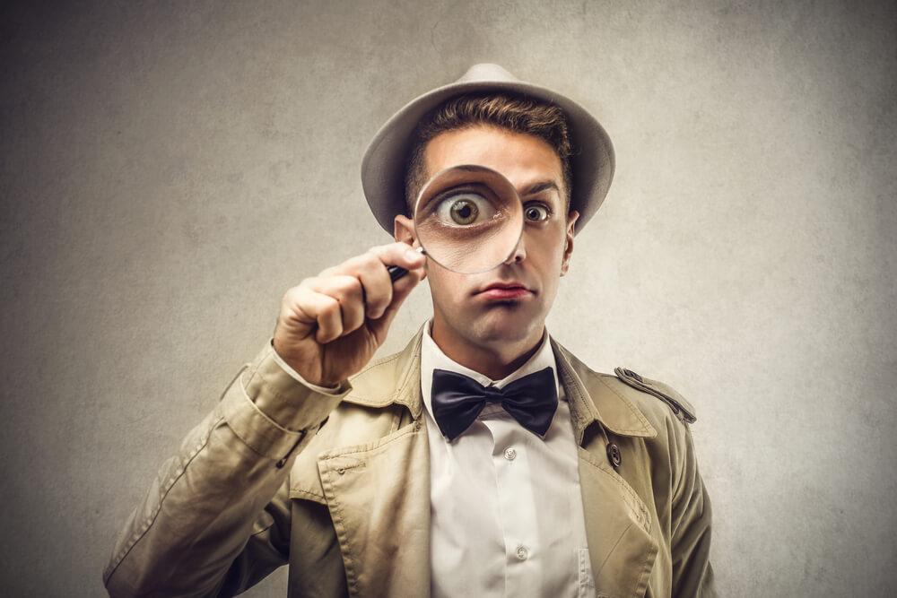 外国人探偵が虫眼鏡を使って永住権の不許可理由を調査