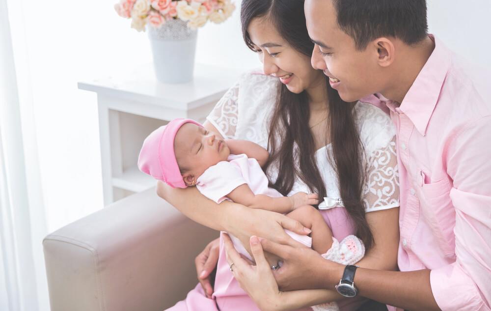 アジア系の国際結婚夫婦が赤ちゃんを笑顔で囲んでいる