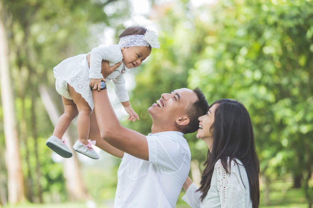 公園で赤ちゃんを抱きあげる国際結婚夫婦