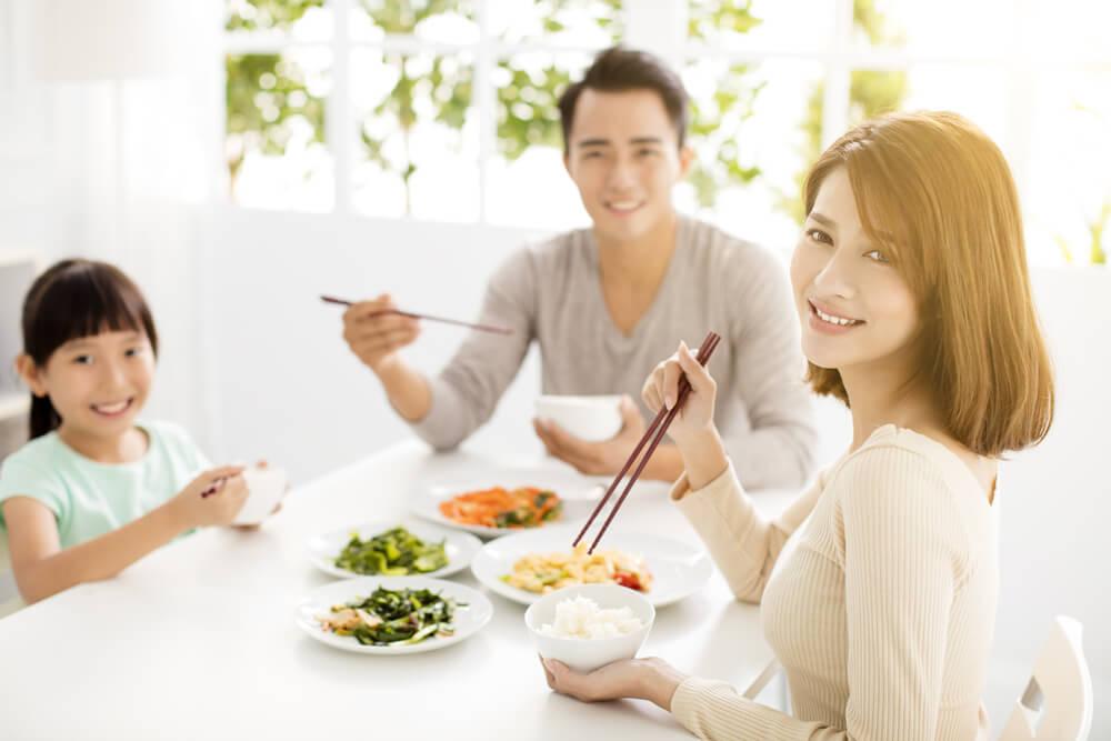 「永住権取得の要件は?」「永住ビザを取得するためには3要件必要」アジア系の3人家族が笑顔で食卓を囲んでいる