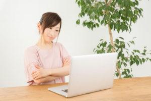 パソコンの前で首をかしげる女性