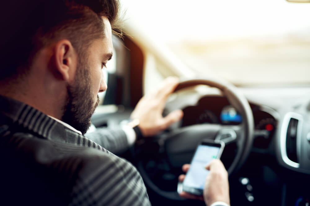「永住権取得の要件は?」「永住ビザを取得するためには3要件必要」スマートフォンを操作しながら、車の運転をしている外国人男性
