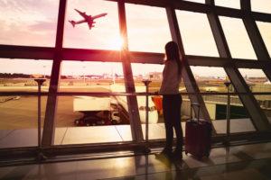 「永住権取得の要件は?」「永住ビザを取得するためには3要件必要」キャリーバッグを引きながら、離陸する飛行機を眺める外国人女性