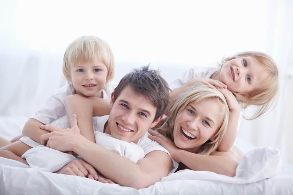 「永住権取得の要件は?」「永住ビザを取得するためには3要件必要」ベッドで笑顔で戯れる外国人の4人家族