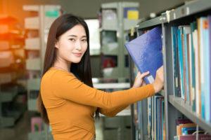 圧倒的なシェアを誇る中国人留学生が、図書館で勉強をしている