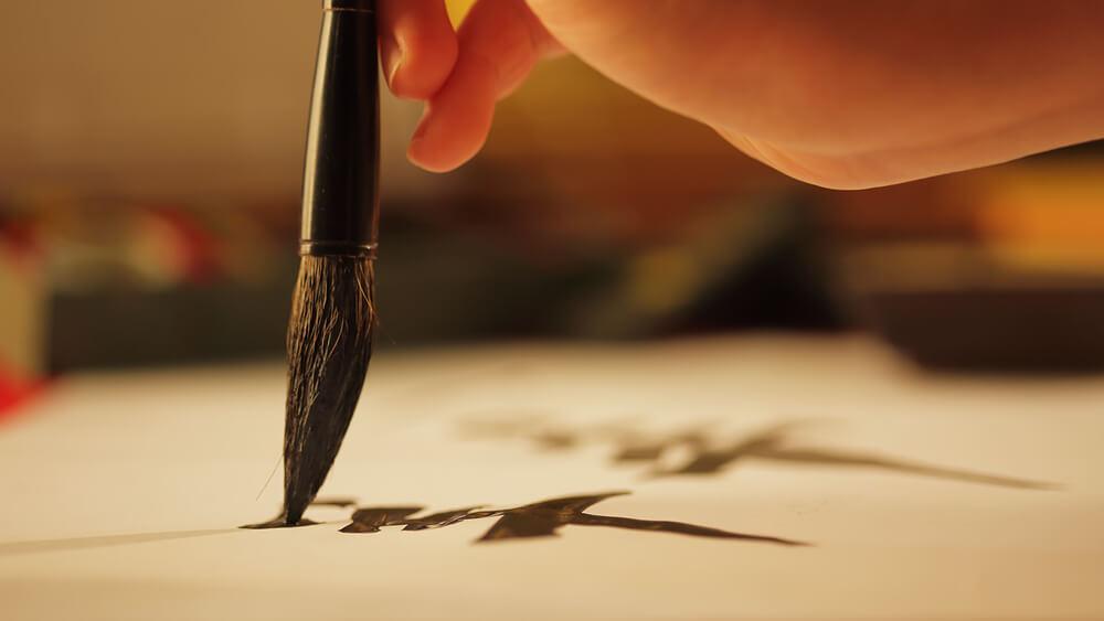 永住申請理由書のために、正しい日本語を丁寧に書く書道の練習をする外国人