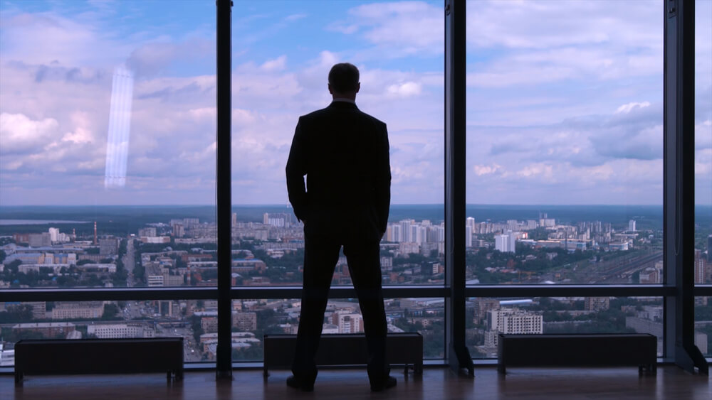 ビルの展望台から街を見下ろすビジネスマン