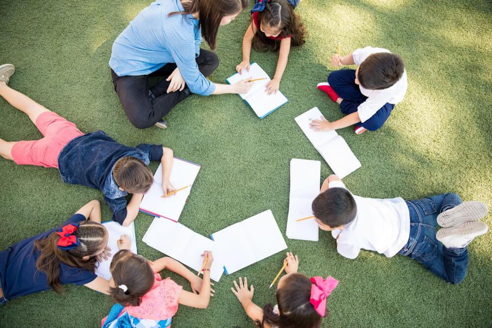「永住権取得の要件は?」「永住ビザを取得するためには3要件必要」芝生の上で子供たちに英語を教える外国人女性