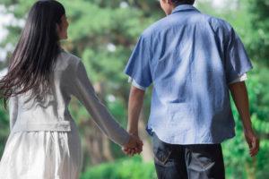 手をつないで歩く若いカップルの後ろ姿