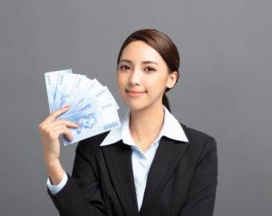 札束で顔を仰ぐ美人なアジア系女性