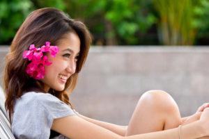 花飾りを髪につけ、はにかむアジア系女性