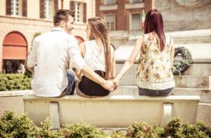 目の前の女性と話しながら、その女性の後ろで別の女性と手をつないでいる男性(跛行婚による重婚)