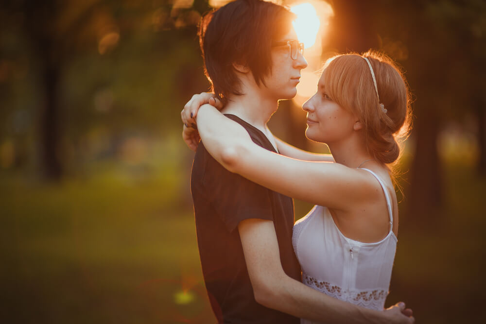 夕日が差し込む森の中で、静かに抱き合う国際結婚カップル