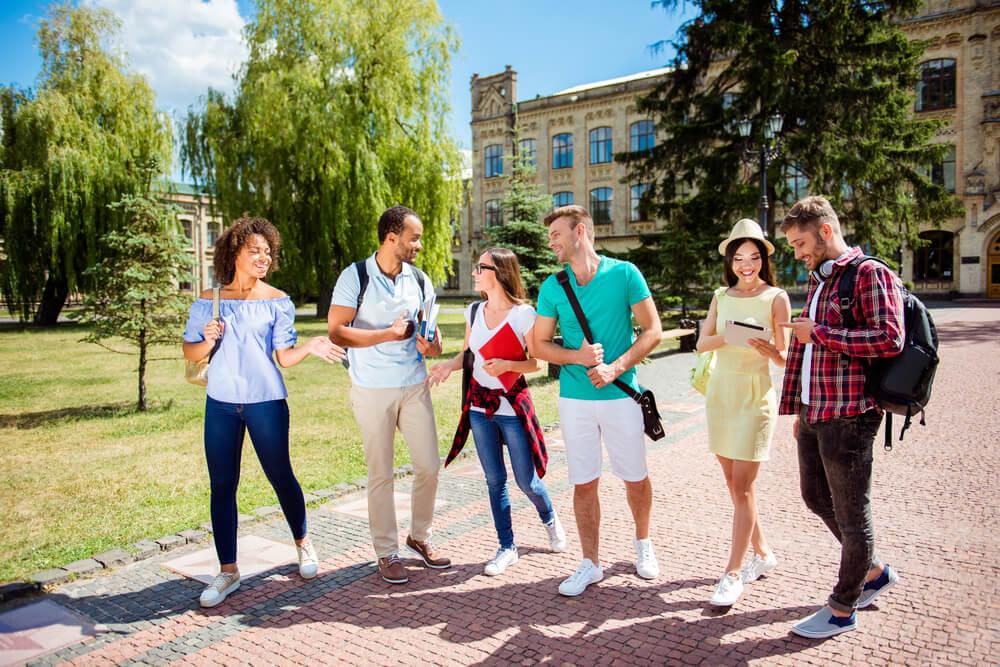 晴れ渡った中、キャンパスを談笑しながら歩くいろいろな国籍の学生たち