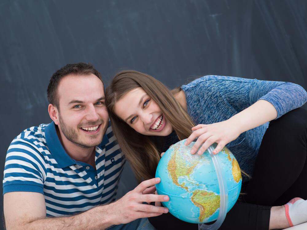 跛行婚について知りたがっている、地球儀を二人で囲んで微笑んでいる外国人カップル