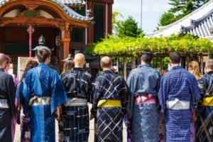 国際結婚は減少していても、インバウンドは増加中!浴衣姿で神社の門の前に並ぶ外国人観光客たち