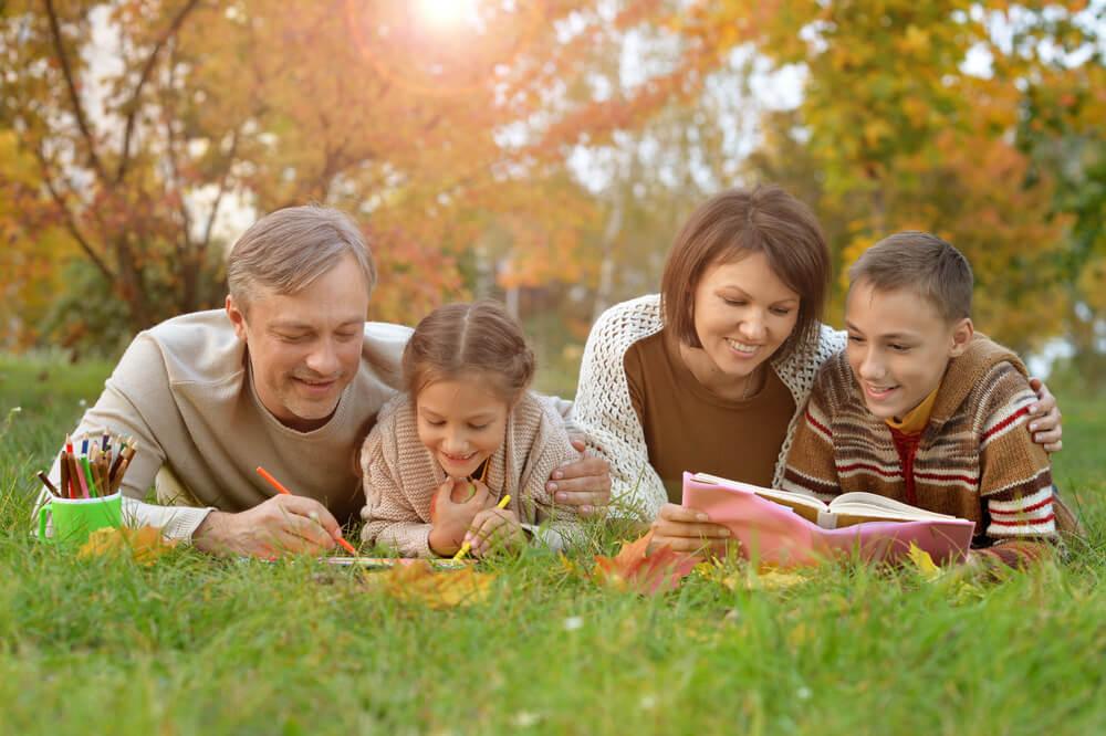 芝生の上に横になりながら本を読む外国人一家