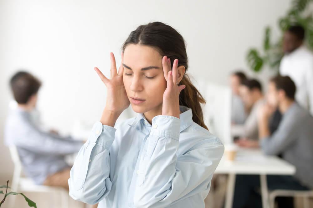 日本語を使う職場で疲れ果てている外国人女性