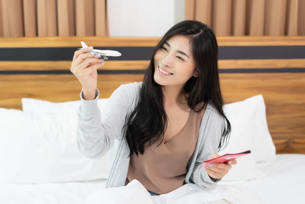 楽しそうに旅行計画を立てるアジア人女性
