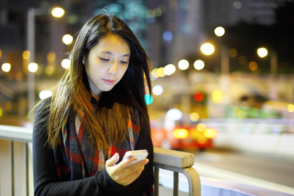 夜の街で暗い表情でスマホをいじる中国人女性