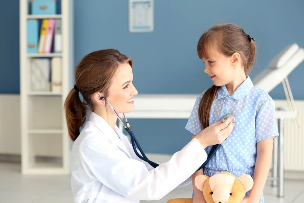 子供に聴診器を当てて笑顔で話しかける女医さん