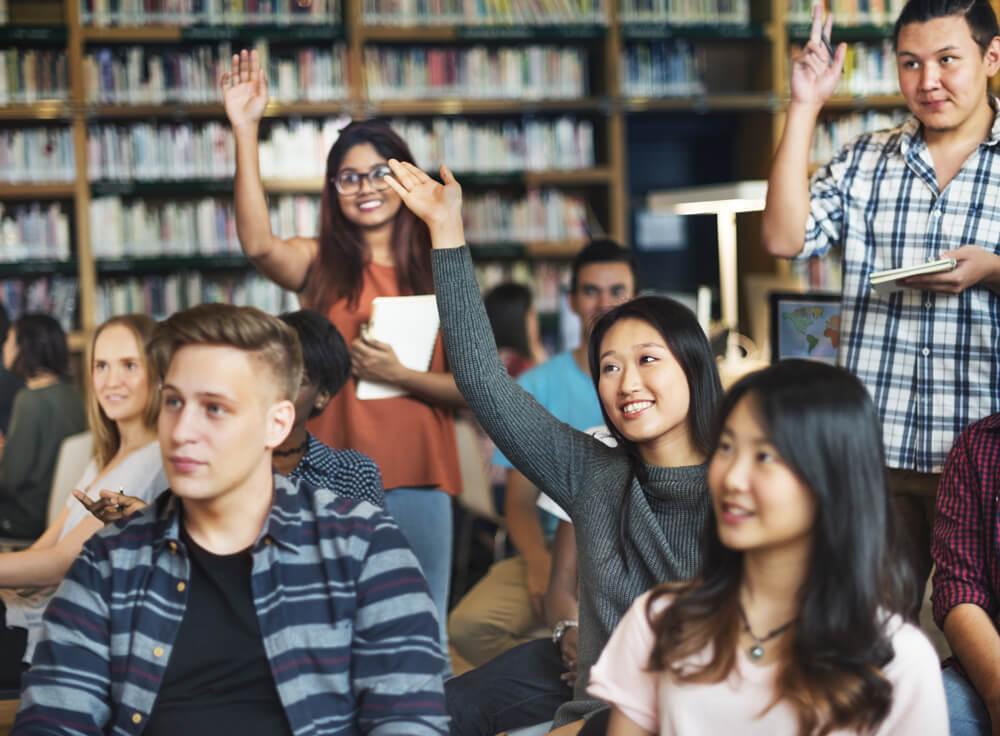 従来の日本語試験には限界があり、外務省は外国人労働者向けの新しい日本語試験を創設予定。教室で手を挙げて授業に参加する外国人たち