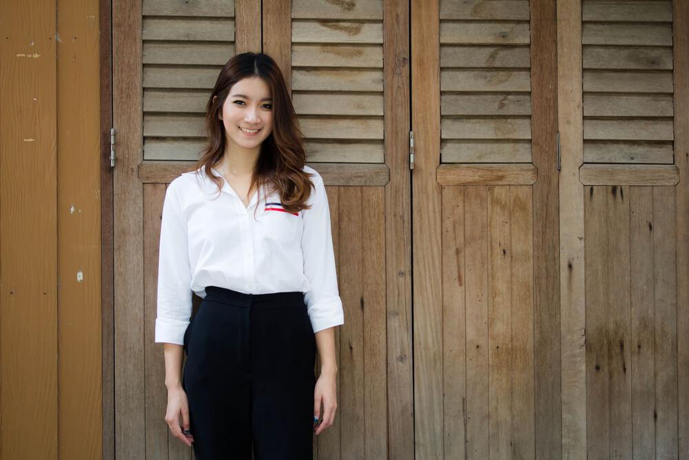 木製の扉前でほほ笑む中国人女性