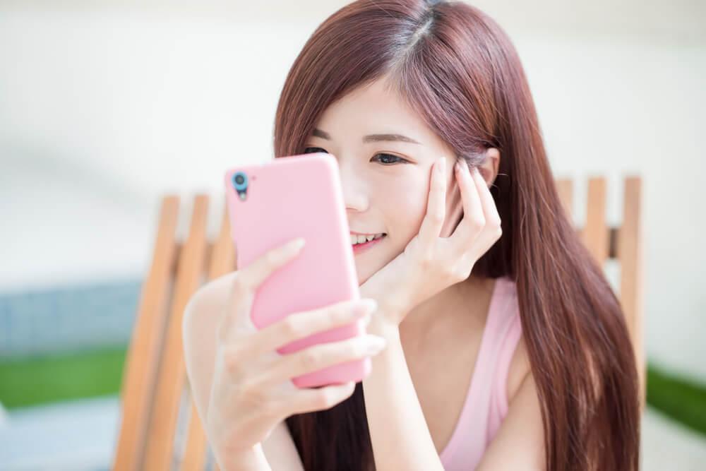 自分の顔を自撮りするアジア人の若い女性