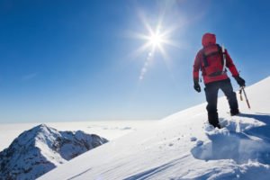 晴れた雪山を登山途中の男性