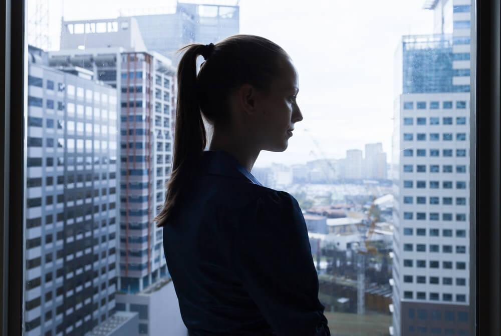 マンションの窓際に立ち、物憂げに階下を眺める外国人女性