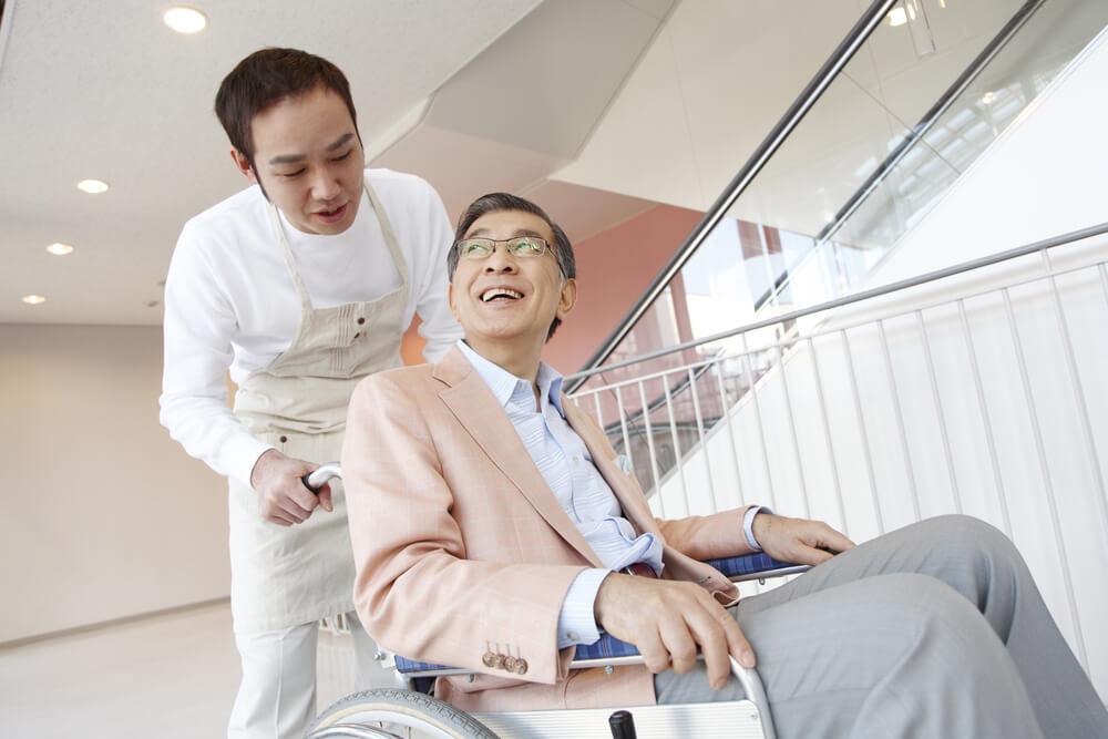 アジア人の若者介護士が、車いすの日本人男性を介護している