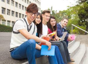 5人の留学生がならんで座って、こちらに向かって微笑んでいる