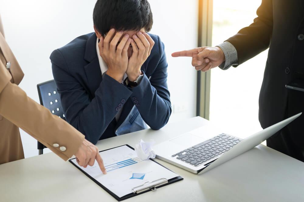 同僚に責め立てられて、顔を覆う日本人男性(自分の気持ちを表現することが苦手な人は、国際結婚で離婚しやすい人)