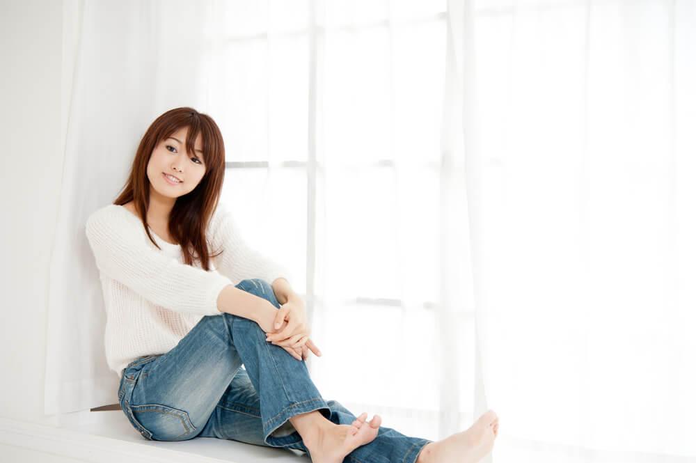 窓辺に座っているジーンズ姿のアジア人女性