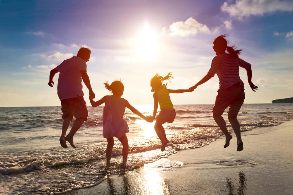 国際結婚を両親に反対されたが、説得の末祝福された一家が、夕方の浜辺で、地平線に向かって家族でジャンプ