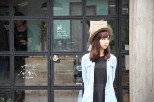 喫茶店の前で待っている日本人女性
