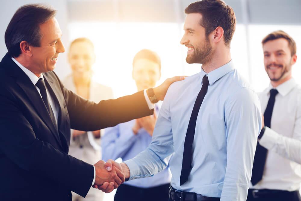 「永住権取得の要件は?」「永住ビザを取得するためには3要件必要」転職をして新しい職場で入社を祝福される外国人ビジネスマン