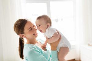外国人の赤ちゃんをお母さんが笑顔で抱きかかえている