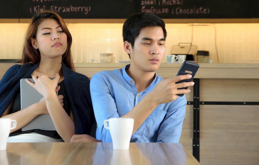 留学生が操作するスマートフォンの画面を覗き見る日本人