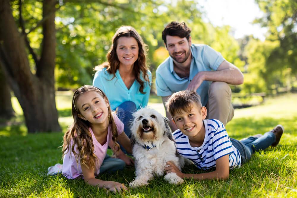 公園で愛犬を囲んで記念撮影をする外国人一家