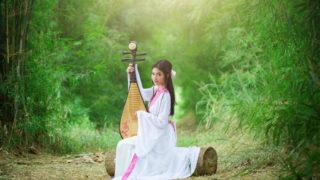 森の中で中国の民族衣装をまとい、弦楽器を奏でる女性