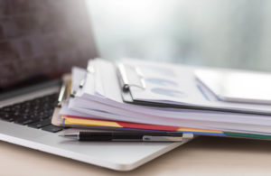 パソコンに置かれた書類の山