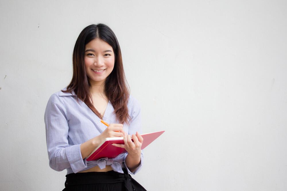 取り寄せる書類をメモしている中国人女性